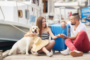 A young married couple,a man with a beard and a pregnant woman,brunette,long straight hair, with a friend,a Labrador dog,awaiting departure on a journey,sitting on the dock with a big blue suitcase waiting for the ship